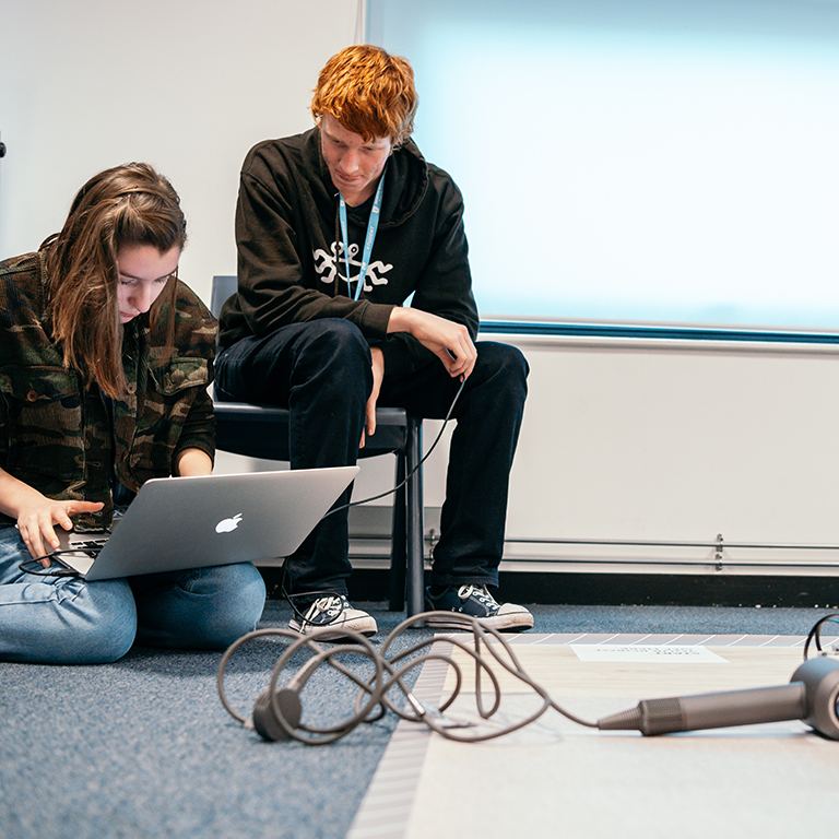 Two sixth form students programming a robot to navigate around a Dyson Supersonic in a James Dyson Foundation robotics workshop.